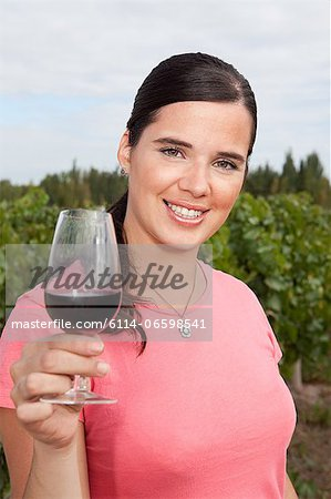 Woman in vineyard with red wine Stock Photo - Premium Royalty-Free, Image code: 6114-06598541