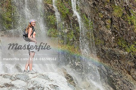 Woman by scenic waterfall Stock Photo - Premium Royalty-Free, Image code: 6114-06598562