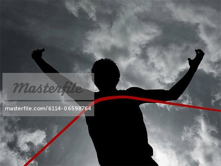 Silhouette of athlete at finish line Stock Photo - Premium Royalty-Free, Image code: 6114-06598764