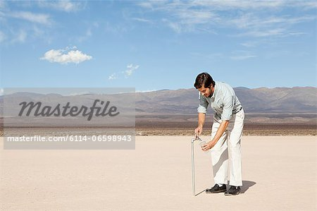 Man using facuet in desert landscape Stock Photo - Premium Royalty-Free, Image code: 6114-06598943