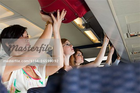 Passengers putting luggage in lockers on plane Stock Photo - Premium Royalty-Free, Image code: 6114-06599092