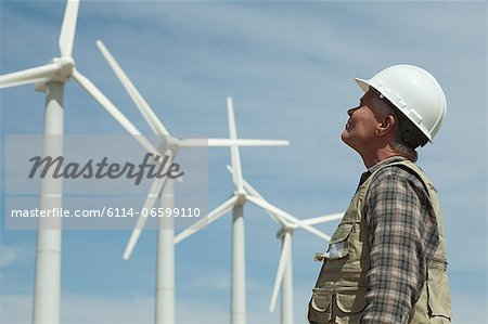 Man in hard hat looking at wind turbines Stock Photo - Premium Royalty-Free, Image code: 6114-06599110