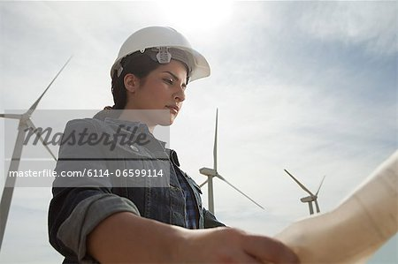 Female engineer at wind farm with plans Stock Photo - Premium Royalty-Free, Image code: 6114-06599114