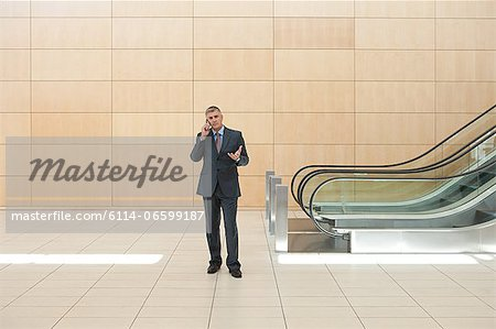 Businessman on cellphone by escalator Stock Photo - Premium Royalty-Free, Image code: 6114-06599187