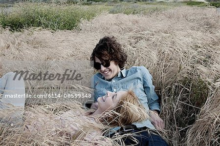 Young couple lying in grassy field Stock Photo - Premium Royalty-Free, Image code: 6114-06599348