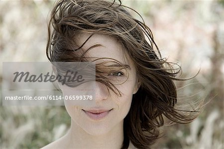 Young brunette woman alone outdoors, portrait Stock Photo - Premium Royalty-Free, Image code: 6114-06599378