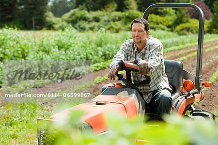 Farmer on tractor in field Stock Photo - Premium Royalty-Free, Image code: 6114-06599867