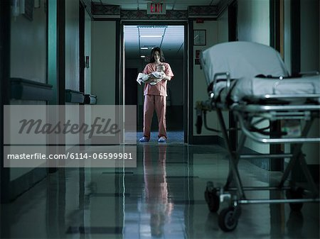 Nurse holding newborn baby in hospital corridor Stock Photo - Premium Royalty-Free, Image code: 6114-06599981