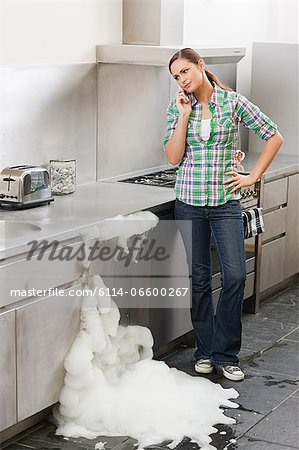 Young woman on phone with overflowing dishwasher Stock Photo - Premium Royalty-Free, Image code: 6114-06600267
