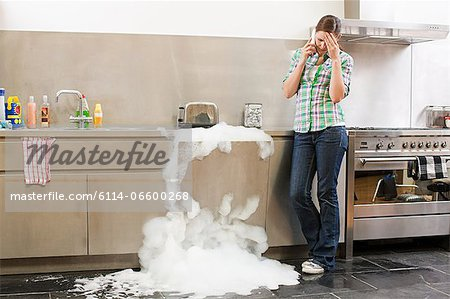 Young woman on phone with overflowing dishwasher Stock Photo - Premium Royalty-Free, Image code: 6114-06600268