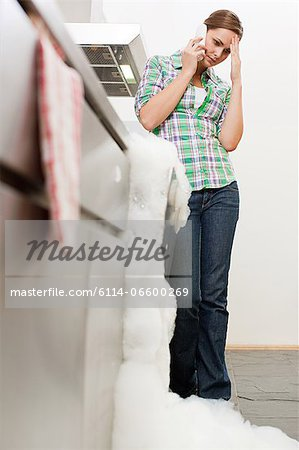 Young woman on phone with overflowing dishwasher Stock Photo - Premium Royalty-Free, Image code: 6114-06600269