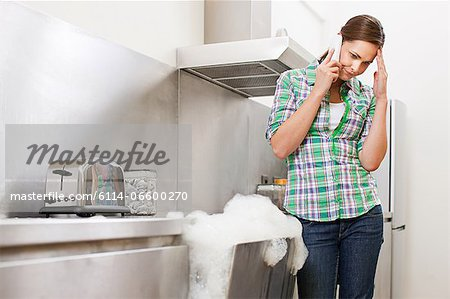 Young woman on phone with overflowing dishwasher Stock Photo - Premium Royalty-Free, Image code: 6114-06600270