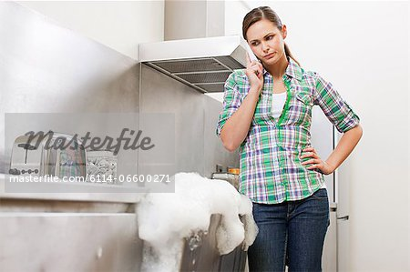 Young woman on phone with overflowing dishwasher Stock Photo - Premium Royalty-Free, Image code: 6114-06600271