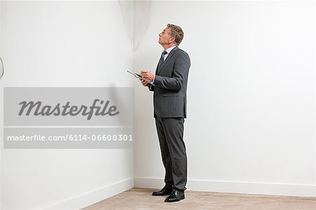 Mature man examining damp patch on wall Stock Photo - Premium Royalty-Free, Image code: 6114-06600301
