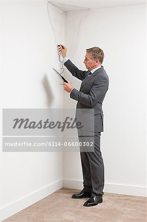 Mature man examining damp patch on wall Stock Photo - Premium Royalty-Free, Image code: 6114-06600302