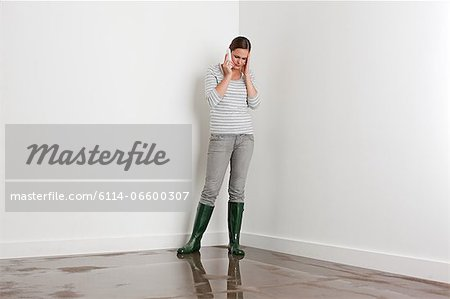 Young woman on flooded floor Stock Photo - Premium Royalty-Free, Image code: 6114-06600307
