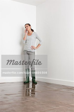 Young woman on flooded floor Stock Photo - Premium Royalty-Free, Image code: 6114-06600308