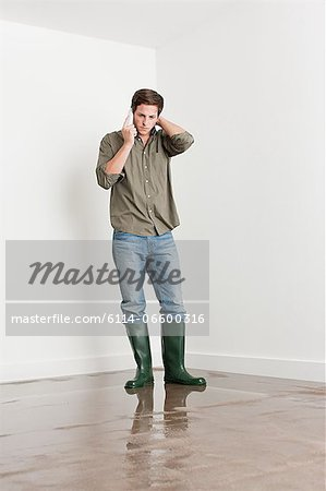Young man on flooded floor Stock Photo - Premium Royalty-Free, Image code: 6114-06600316
