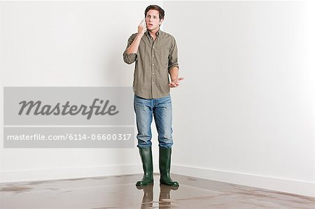 Young man on flooded floor Stock Photo - Premium Royalty-Free, Image code: 6114-06600317