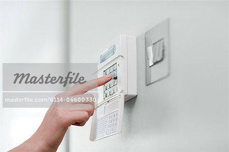 Woman setting burglar alarm Stock Photo - Premium Royalty-Free, Image code: 6114-06600330
