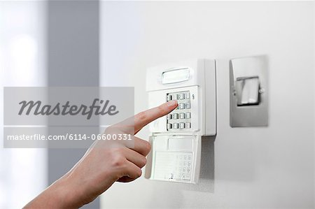 Woman setting burglar alarm Stock Photo - Premium Royalty-Free, Image code: 6114-06600331