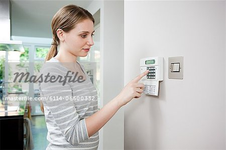 Woman setting burglar alarm Stock Photo - Premium Royalty-Free, Image code: 6114-06600332