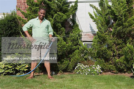 Man watering grass with hosepipe Stock Photo - Premium Royalty-Free, Image code: 6114-06600449