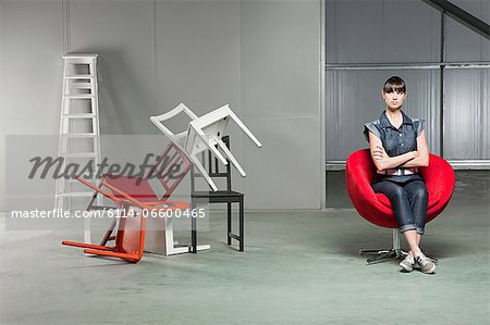 Young woman sitting on red swivel chair Stock Photo - Premium Royalty-Free, Image code: 6114-06600465