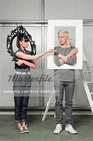 Young couple holding black and white picture frames Stock Photo - Premium Royalty-Free, Image code: 6114-06600507