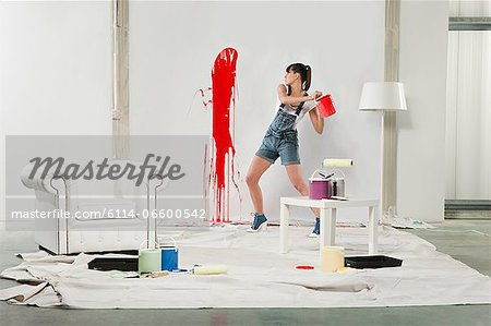 Young woman splashing red paint on white wall Stock Photo - Premium Royalty-Free, Image code: 6114-06600542