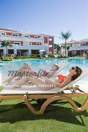 Two women sunbathing on sunloungers at poolside Stock Photo - Premium Royalty-Free, Image code: 6114-06600601
