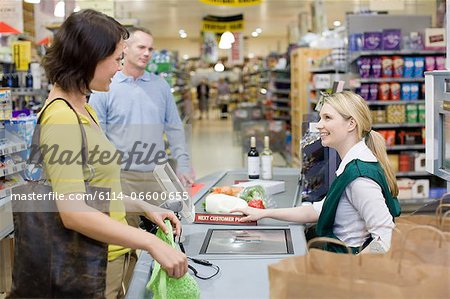Cashier and customers at supermarket checkout Stock Photo - Premium Royalty-Free, Image code: 6114-06600655