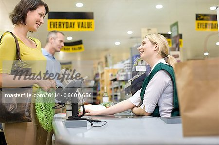 Cashier and customers at supermarket checkout Stock Photo - Premium Royalty-Free, Image code: 6114-06600656