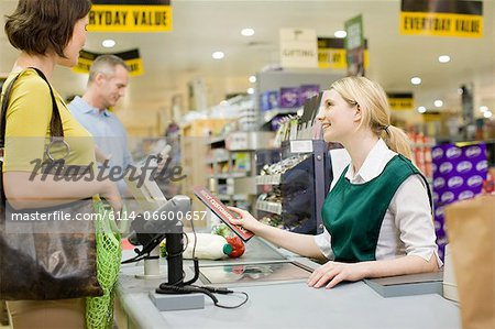 Cashier and customers at supermarket checkout Stock Photo - Premium Royalty-Free, Image code: 6114-06600657