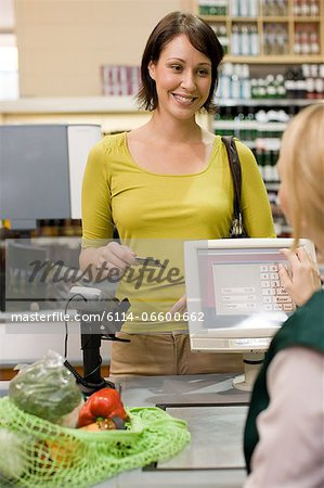 Woman at supermarket checkout Stock Photo - Premium Royalty-Free, Image code: 6114-06600662