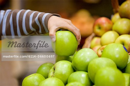 Child holding an apple Stock Photo - Premium Royalty-Free, Image code: 6114-06600697