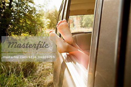 Bare feet sticking out of a car window Stock Photo - Premium Royalty-Free, Image code: 6114-06600759