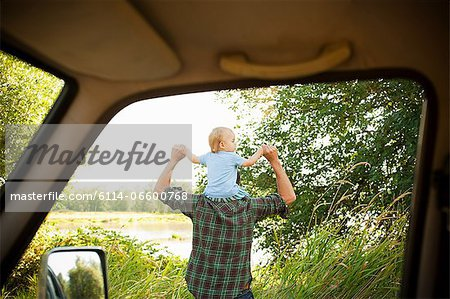 Father with son on shoulders, viewed from a car Stock Photo - Premium Royalty-Free, Image code: 6114-06600768