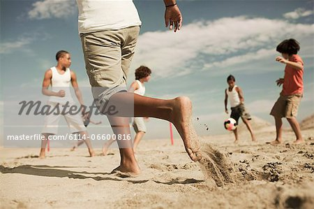 Boys playing football on beach Stock Photo - Premium Royalty-Free, Image code: 6114-06600816