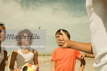 Boys tossing a coin Stock Photo - Premium Royalty-Free, Image code: 6114-06600826