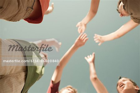 Boys doing high five, low angle view Stock Photo - Premium Royalty-Free, Image code: 6114-06600840