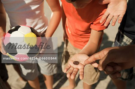 Boys tossing a coin Stock Photo - Premium Royalty-Free, Image code: 6114-06600844