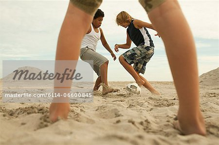 Boys playing football on beach Stock Photo - Premium Royalty-Free, Image code: 6114-06600845