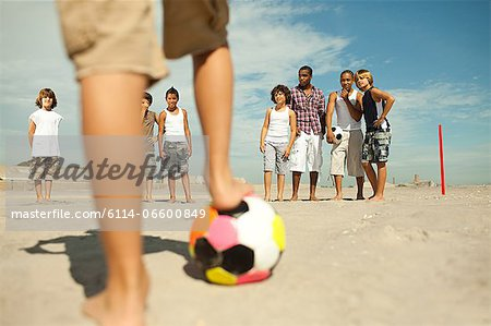 Boys playing football on beach Stock Photo - Premium Royalty-Free, Image code: 6114-06600849