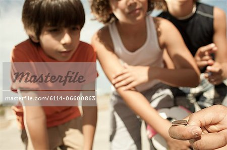 Boys tossing a coin Stock Photo - Premium Royalty-Free, Image code: 6114-06600863