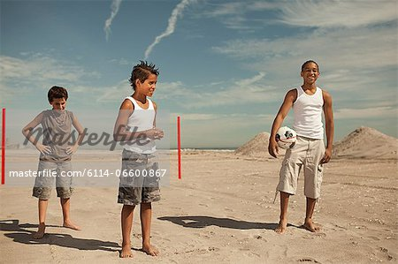Boys standing on beach with football Stock Photo - Premium Royalty-Free, Image code: 6114-06600867