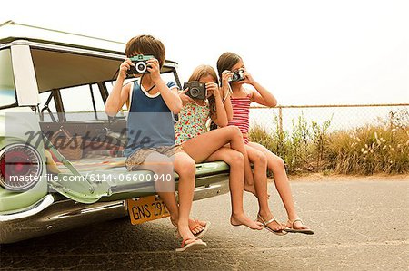Three children sitting on back of estate car taking photographs Stock Photo - Premium Royalty-Free, Image code: 6114-06600940