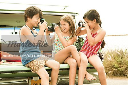 Three children sitting on back of estate car taking photographs Stock Photo - Premium Royalty-Free, Image code: 6114-06600941
