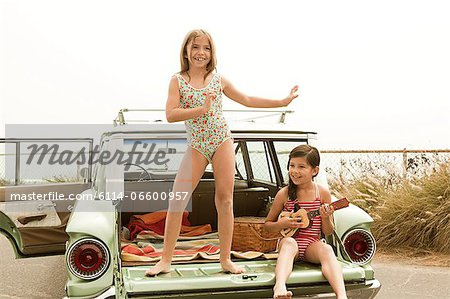 Girl dancing on car boot, another girl playing guitar Stock Photo - Premium Royalty-Free, Image code: 6114-06600957