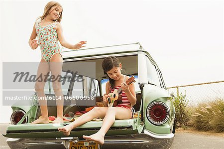 Girl dancing on car boot, another girl playing guitar Stock Photo - Premium Royalty-Free, Image code: 6114-06600958